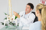 Content doctor showing a patient something on skeleton model