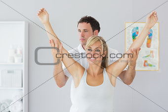 Attractive physiotherapist checking patients arm