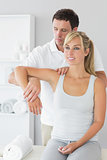 Good looking physiotherapist controlling patients arm