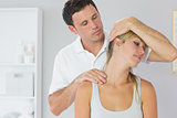 Attractive physiotherapist examining patients neck