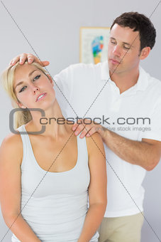 Attractive physiotherapist checking patients neck