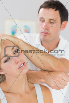 Calm physiotherapist massaging patients neck with elbow
