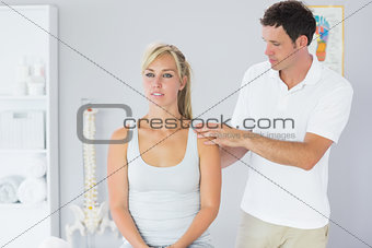 Attractive physiotherapist examining patients back