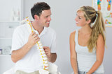 Smiling physiotherapist showing patient something on skeleton model