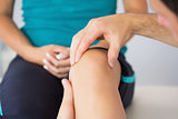 Physiotherapist controlling patients knee