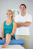 Attractive physiotherapist and patient posing for camera