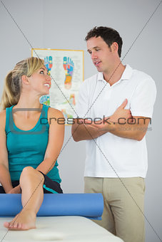 Attractive physiotherapist and patient looking at each other