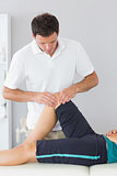 Physiotherapist examining knee of a patient