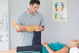 Good looking physiotherapist controlling knee of a patient