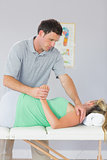 Handsome physiotherapist manipulating patients arm behind back