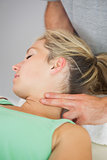 Physiotherapist applying pressure to patients neck