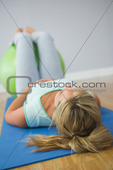 Blonde woman lying on floor doing exercise with exercise ball