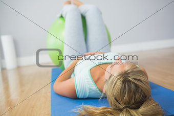 Blonde woman doing exercise with exercise ball on the floor
