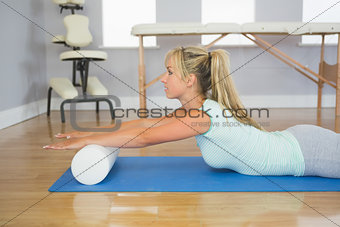 Blonde patient lying on floor doing exercise