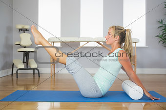 Blonde patient doing exercise on the floor