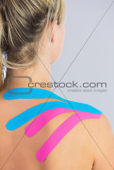 Close up of patients shoulder with applied pink and blue kinesio tape