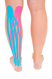 Patients leg with applied pink and blue kinesio tape