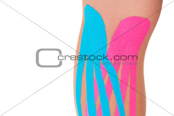Close up of patients knee with applied pink and blue kinesio tape