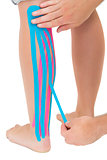 Physiotherapist applying pink and blue kinesio tape on patients leg