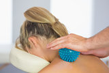 Physiotherapist massaging female patient with blue massage ball