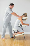 Masseur treating shoulders of client in massage chair