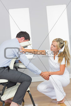 Masseuse massaging clients arm in massage chair
