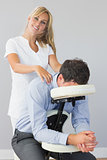 Smiling masseuse treating clients neck in massage chair