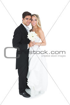 Cute young married couple posing holding a white bouquet
