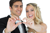 Cheerful married couple showing their wedding rings