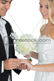 Smiling bridegroom putting the wedding ring on his wifes finger