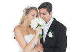 Young married couple posing having a sniff of the bouquet