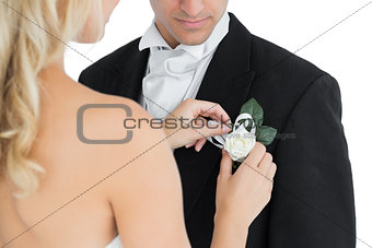 Blonde bride pinning a flower on the suit of her husband
