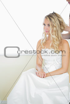Beautiful blonde bride being prepared for the wedding