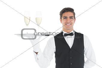 Smiling attractive waiter holding a tray with champagne glasses on it