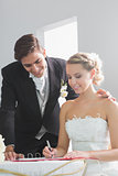 Young beautiful bride signing wedding register