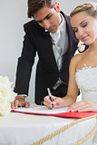 Young smiling bride signing wedding contract