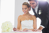 Happy young couple signing wedding register