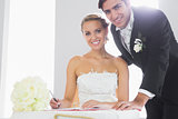 Attractive couple signing wedding register