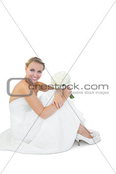 Beautiful young bride sitting on floor holding a bouquet