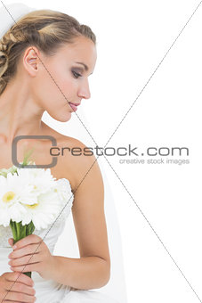Attractive blonde bride holding a bouquet