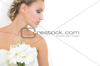 Thoughtful pretty bride holding a bouquet looking down