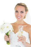 Cheerful bride holding a bouquet and a champagne glass