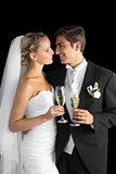 Gorgeous young married couple posing holding champagne glasses