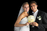 Happy young married couple posing holding champagne glasses