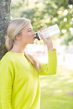 Fit calm blonde drinking from water bottle
