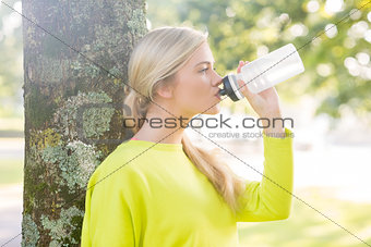Fit peaceful blonde drinking from water bottle