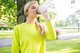 Fit peaceful blonde drinking from sports bottle