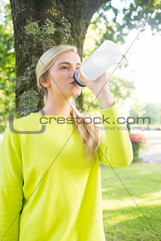 Fit calm blonde drinking from sports bottle