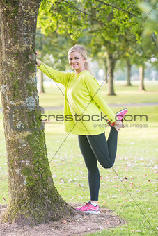 Fit smiling blonde stretching leg