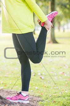Fit woman stretching leg